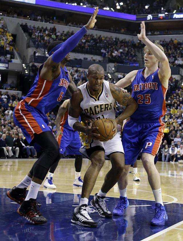 Indiana Pacers forward David West, center is trapped by Detroit Pistons forward Josh Smith, left, and forward Kyle Singler in the second half of an NBA basketball game in Indianapolis, Monday, Dec. 16, 2013. The Pistons defeated the Pacers 101-96. (AP Photo/Michael Conroy)