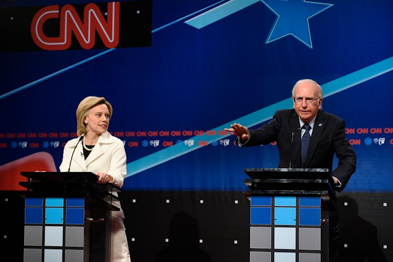 Kate McKinnon (Left) stands at a podium as Elizabeth Warren and Larry David (Right) stands at a podium as Bernie Sanders