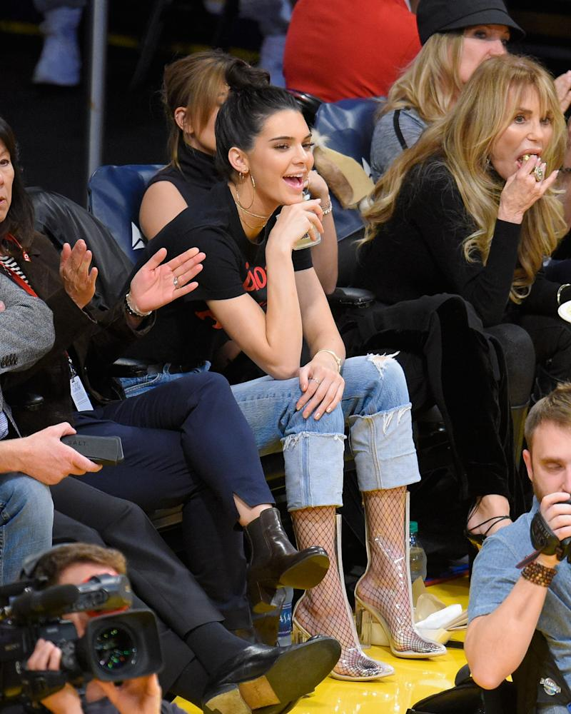 "In a ""Dior Addict"" graphic tee paired with vintage Levi's jeans — both from What Goes Around Comes Around — and Yeezy-inspired clear boots, Kendall Jenner channeled Rihanna a basketball game between the Memphis Grizzlies and the Los Angeles Lakers."