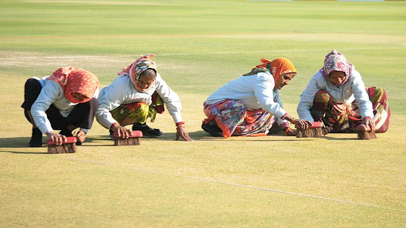 Four women, pictured here scrubbing the pitch with hand-held brushes at the Saurashtra Cricket Association Stadium in Rajkot.