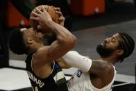 Milwaukee Bucks' Giannis Antetokounmpo and LA Clippers' Paul George battle for the ball during the first half of an NBA basketball game Sunday, Feb. 28, 2021, in Milwaukee. (AP Photo/Morry Gash)