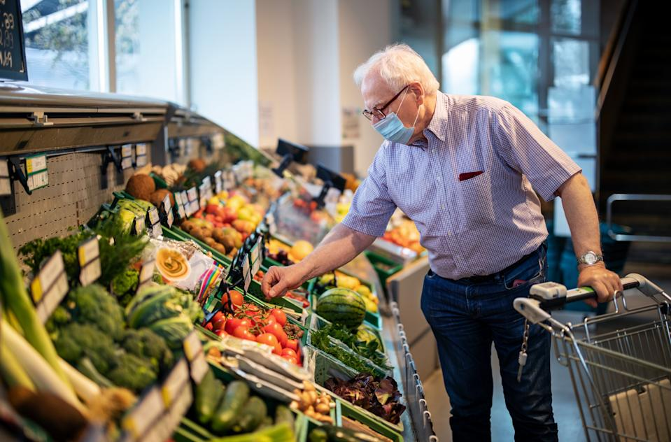 Senior man with face mask buying vegetables in a local supermarket. Elderly man doing home shopping in grocery store with a shopping cart.
