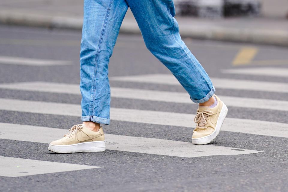 PARIS, FRANCE - JULY 04: A passerby wears blue cuffed denim jeans, beige Nike sneakers shoes, on July 04, 2020 in Paris, France. (Photo by Edward Berthelot/Getty Images)