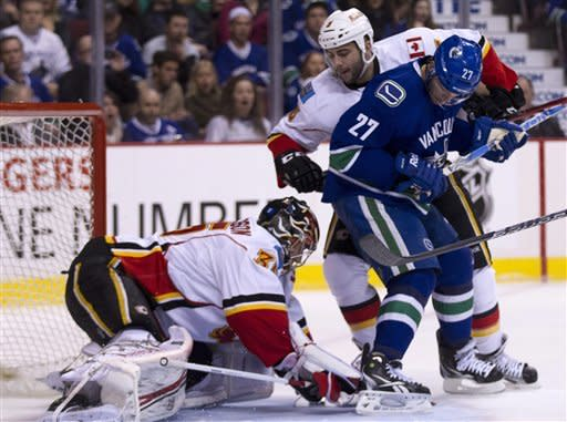 Vancouver Canucks center Manny Malhotra (27) tries to get a shot past Calgary Flames defenseman Mark Giordano (5) and Calgary Flames goalie Henrik Karlsson (35) during first period NHL hockey action at Rogers Arena in Vancouver, British Columbia, Saturday, March, 31, 2012. (AP Photo/The Canadian Press, Jonathan Hayward)