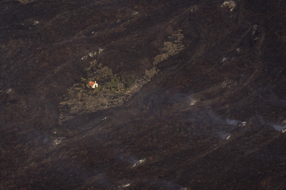 Lava from a volcano surrounds a house on the island of La Palma in the Canaries, Spain, Thursday, Sept. 23, 2021. The Sunday eruption on a small Spanish island in the Atlantic Ocean forced the evacuation of thousands. (AP Photo/Emilio Morenatti, Pool)