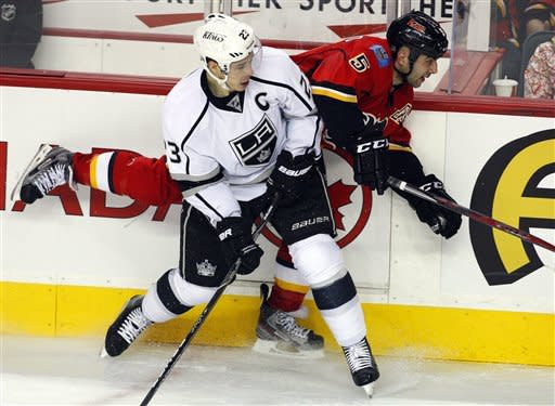 Los Angeles Kings' Dustin Brown, left, checks Calgary Flames' Mark Giordano during third period NHL hockey action in Calgary, Alberta, Wednesday, Feb. 20, 2013. The Los Angeles Kings beat the Calgary Flames 3-1. (AP Photo/THE CANADIAN PRESS/Jeff McIntosh)