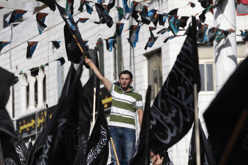 """Palestinian supporters of Hizbut-Tahrir, or Party of Liberation, shout slogans during a rally in the West Bank city of Ramallah, Tuesday , June 4, 2013. Arabic words on the flags read: """"There is no god but God, and Mohammed is his prophet."""" A senior Palestinian official says the West Bank government will try to bring Israel up on charges through the U.N. if American attempts to restart peace talks fail. (AP Photo/Majdi Mohammed)"""