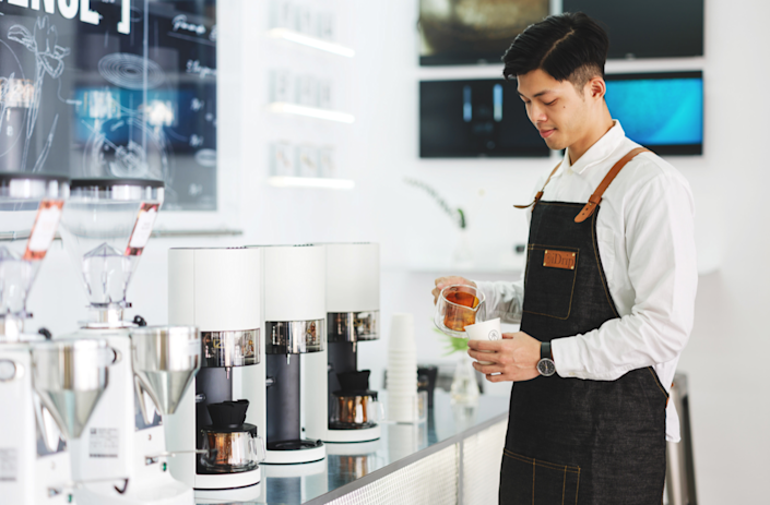 Expert Barista scientifically prepares gourmet coffee at iDrip's Smart Pour-Over Coffeemaker exhibition space.