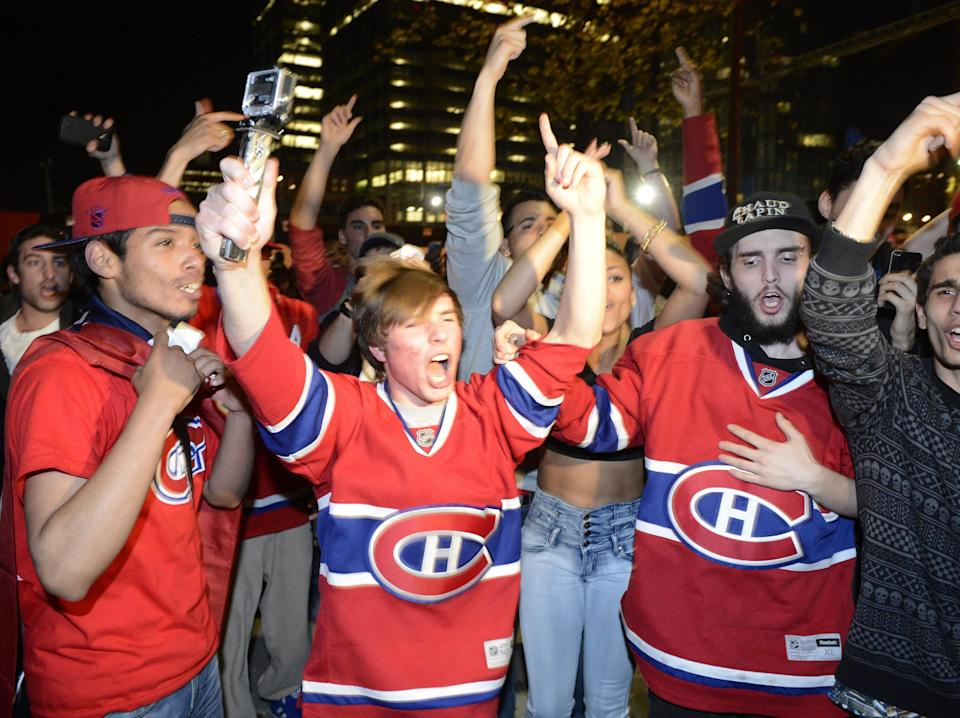Montreal Canadiens fans celebrate their team's third goal against the Boston Bruins, as they watch the broadcast of the game on a large TV screen in Montreal on Wednesday, May 14, 2014. (AP Photo/The Canadian Press, Ryan Remiorz)