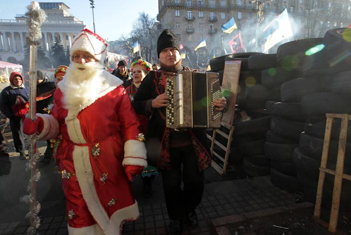 A man dressed as Grandfather Frost, the Ukrainian equivalent of Santa Claus, and a man playing the accordion walk through a protest camp in the Independence Square in Kiev in Kiev, Ukraine, Thursday, Dec. 26, 2013. (AP Photo/Sergei Chuzavkov)