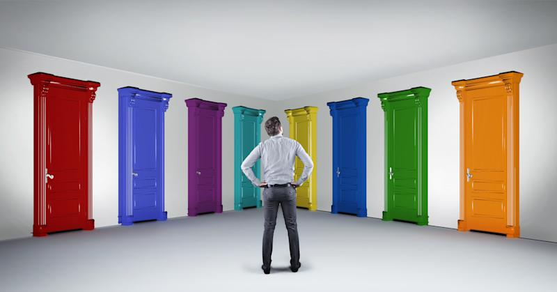 Businessman standing in hallway in front of multicolored doors. Concept of hard choice and opportunities.