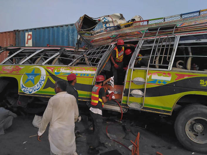 In this handout photo released by Punjab Province's Emergency Service Rescue 11222, shows rescue workers at the site of a deadly bus accident near Dera Ghazi Khan, Pakistan, Monday, July 19, 2021. The speeding bus carrying mostly laborers traveling home for a major Muslim holiday rammed into a container truck on a busy highway in central Pakistan, killing and injuring dozens, police and rescue officials said. (Emergency Service Rescue 1122 via AP)