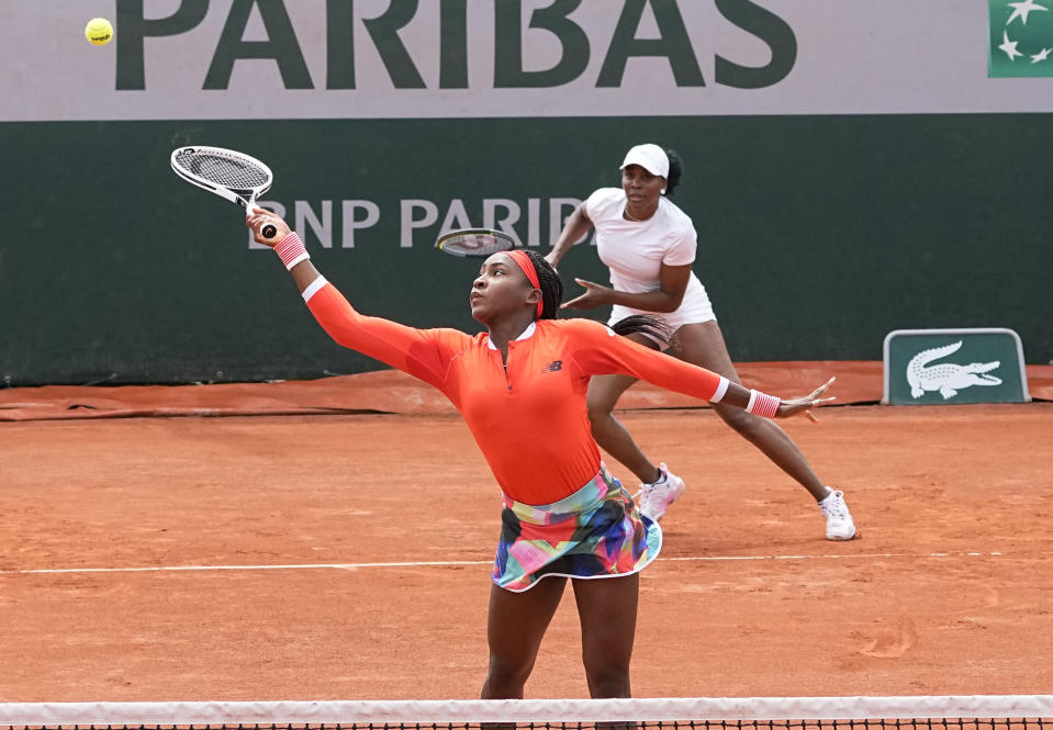 Coco Gauff left, reaches for the ball with doubles partner of Venus Williams, of the United States as they play against EllenPerez of Australia and Saisai Zheng of China in a first round women's doubles match day four of the French Open tennis tournament at Roland Garros in Paris, France, Wednesday, June 2, 2021. (AP Photo/Michel Euler)
