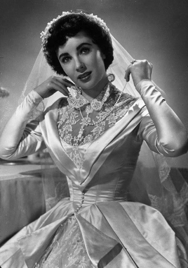 <p>Elizabeth Taylor's wedding dress did not disappoint in the 1950 movie <em>Father of the Bride</em>. That combo of silk, buttons, collar, and lace is everything you could want in a fictional wedding dress. </p>