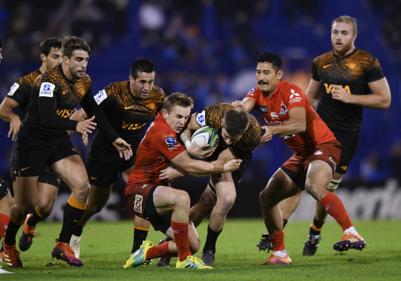 Sebastian Cancelliere of Argentina's Jaguares, center right, is tackled by Hayden Parker of Japan's Sunwolves, center left, during a Super Rugby match in Buenos Aires, Argentina, Friday, June 14, 2019. (AP Photo/Gustavo Garello)