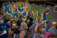 People wearing face masks queue up to be tested for COVID-19, at Vilafranca del Penedes in the Barcelona province, Spain, Monday, August 10, 2020. Spain is facing another surge in coronavirus infections not even two months after beating back the first wave. (AP Photo/Emilio Morenatti)