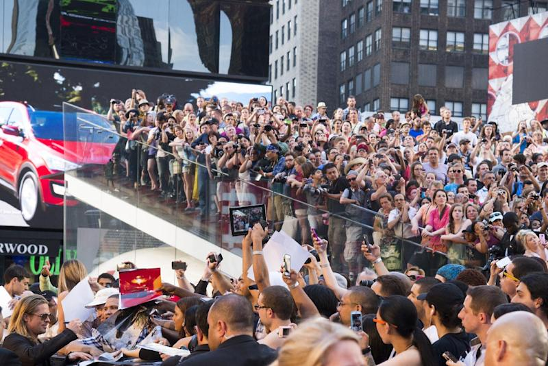 "Actor Brad Pitt, lower left, signs autographs as he arrives to the ""World War Z"" premiere on Monday, June 17, 2013, in New York. (Photo by Charles Sykes/Invision/AP)"