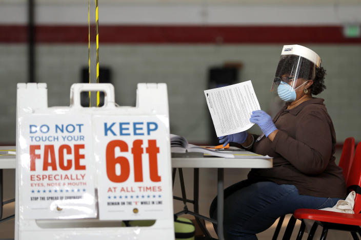 FILE - In this April 28, 2020, file photo, Louisa Boyer, a provisional election judge, reviews paperwork at a voting center at Edmondson High School as voters arrive to cast their ballot in the 7th Congressional District special election in Baltimore. As Republicans roll back access to the ballot, Democratic lawmakers have been quietly moving to expand voting rights. In Virginia, Maryland, Nevada and other states where Democrats have control, lawmakers are pushing to make it easier to cast ballots by mail, increase early voting and require greater oversight over changes to election law. (AP Photo/Julio Cortez, File)