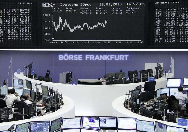 Traders work at their screens in front of the German share price index DAX board at the stock exchange in Frankfurt January 19, 2015. REUTERS/Stringer