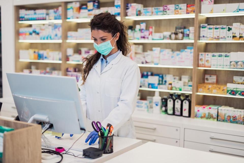 Female pharmacist with protective mask on her face working at pharmacy.
