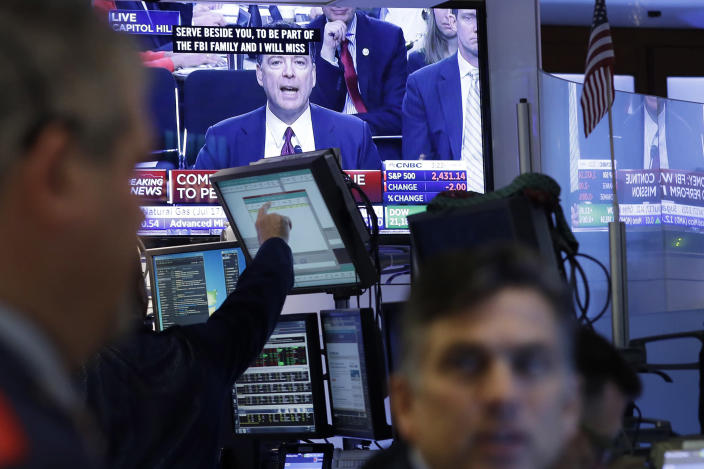 <p>Stock traders at the New York Stock Exchange watch former FBI Director James Comey on a television monitor, Thursday, June 8, 2017, as he testifies before a congressional committee in Washington. (Photo: Mark Lennihan/AP) </p>