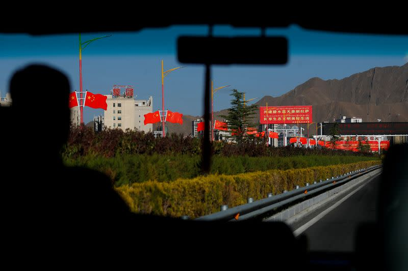 FILE PHOTO: Chinese national flags line the street as a bus carrying foreign journalists on a government tour enters Lhasa