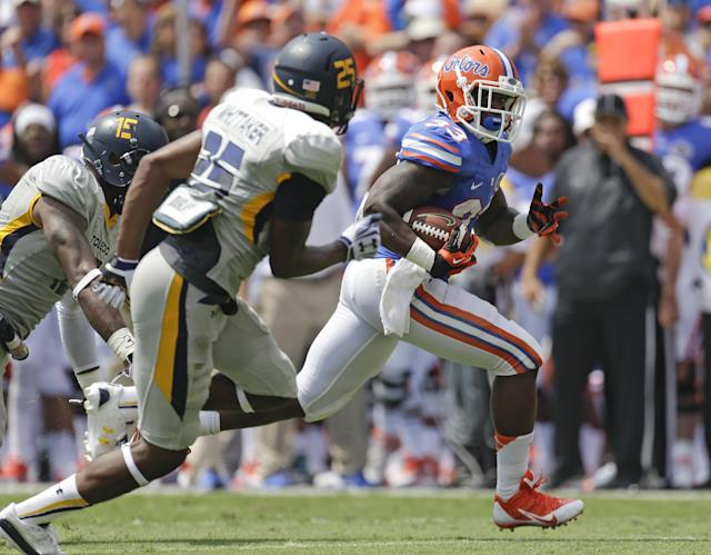 Florida running back Mack Brown gains yardage as he gets past Toledo safety Chaz Whittaker (25) in the first half of an NCAA college football game, Saturday, Aug. 31, 2013, in Gainesville, Fla. (AP Photo/John Raoux)