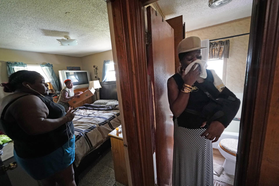 Rakisha Murray, right, reacts as she sees for the first time the damaged home of her sister, Patricia Mingo Lavergne, background, in Lake Charles, La., after they returned from evacuation in the aftermath of Hurricane Laura, Sunday, Aug. 30, 2020. (AP Photo/Gerald Herbert)
