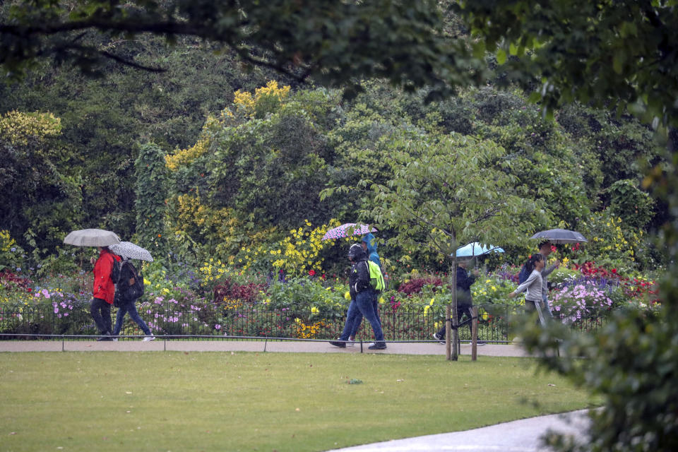 People use umbrellas to cover from the rain in St James's Park, London.