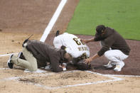San Diego Padres manger Jayce Tingler, right, and a trainer, left, attend to Fernando Tatis Jr., center, after Tatis hurt his shoulder while swinging at a pitch in the third inning of a baseball game against the San Francisco Giants, Monday, April 5, 2021, in San Diego. (AP Photo/Derrick Tuskan)