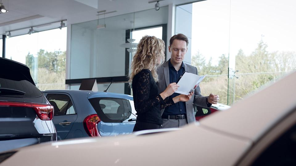 woman asking male car dealer about loan terms