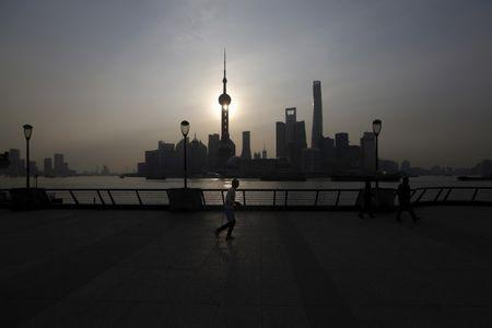 A man runs on the Bund in front of the financial district of Pudong in Shanghai