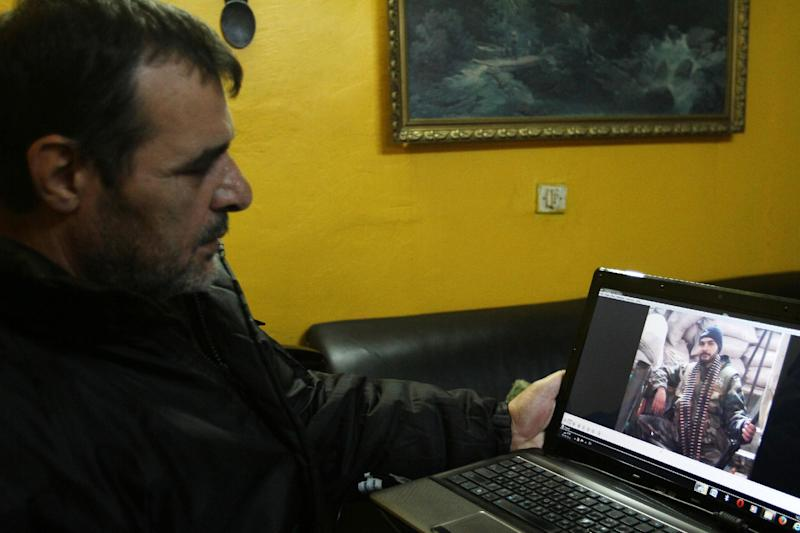 This Saturday, Dec. 7, 2013 photo shows Ahmed Luay, whose son Hassan was killed just over a month ago while fighting in the Syrian army against rebels, watching a video of his son in uniform in Damascus, Syria. Like many government supporters, Luay contends that Syria's nearly 3-year civil war boils down to a fight against foreign jihadis trying to impose Shariah rule, dismissing the opposition view that they are fighting for reforms. (AP Photo)