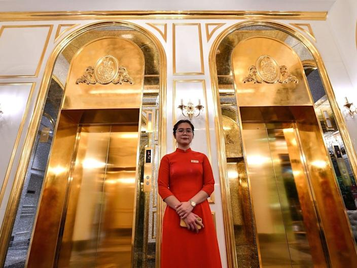 A staff member stands near the lifts in the lobby of the newly-inaugurated Dolce Hanoi Golden Lake hotel in Hanoi, Vietnam, on July 2, 2020.