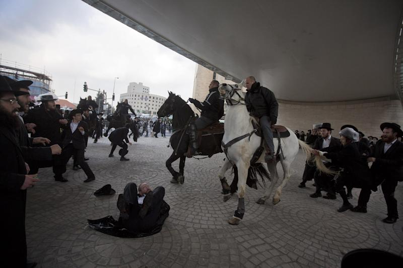 Israeli police officers on horses disperse a crowd of ultra-Orthodox Jewish men during a demonstration in Jerusalem, Thursday, Feb. 6, 2014. Israeli police said thousands of ultra-Orthodox Jews are blocking highways across the country to protest plans to enlist them into the military. (AP Photo/Sebastian Scheiner)