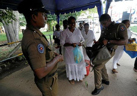 Police officers search the bags of the worshipers at an entrance of the Kelaniya Buddhist temple during Vesak Day, commemorating the birth, enlightenment and death of Buddha, in Colombo, Sri Lanka May 18, 2019. REUTERS/Dinuka Liyanawatte