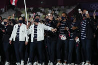 Sue Bird and Eddy Alvares, of the United States of America, carry their country's flag during the opening ceremony in the Olympic Stadium at the 2020 Summer Olympics, Friday, July 23, 2021, in Tokyo, Japan. (AP Photo/Natacha Pisarenko)
