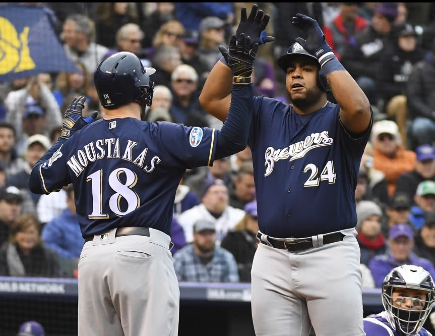 Jesus Aguilar (right) celebrates his home run which helped the Brewers advance to the NLCS. (AP)