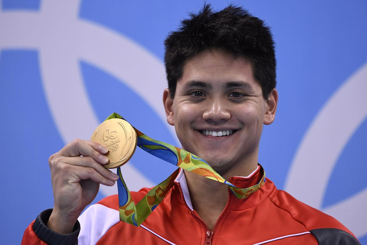 TOPSHOT - Singapore's Joseph Schooling poses with his gold medal on the podium of the Men's 100m Butterfly Final during the swimming event at the Rio 2016 Olympic Games at the Olympic Aquatics Stadium in Rio de Janeiro on August 12, 2016.   / AFP PHOTO / GABRIEL BOUYS        (Photo credit should read GABRIEL BOUYS/AFP via Getty Images)