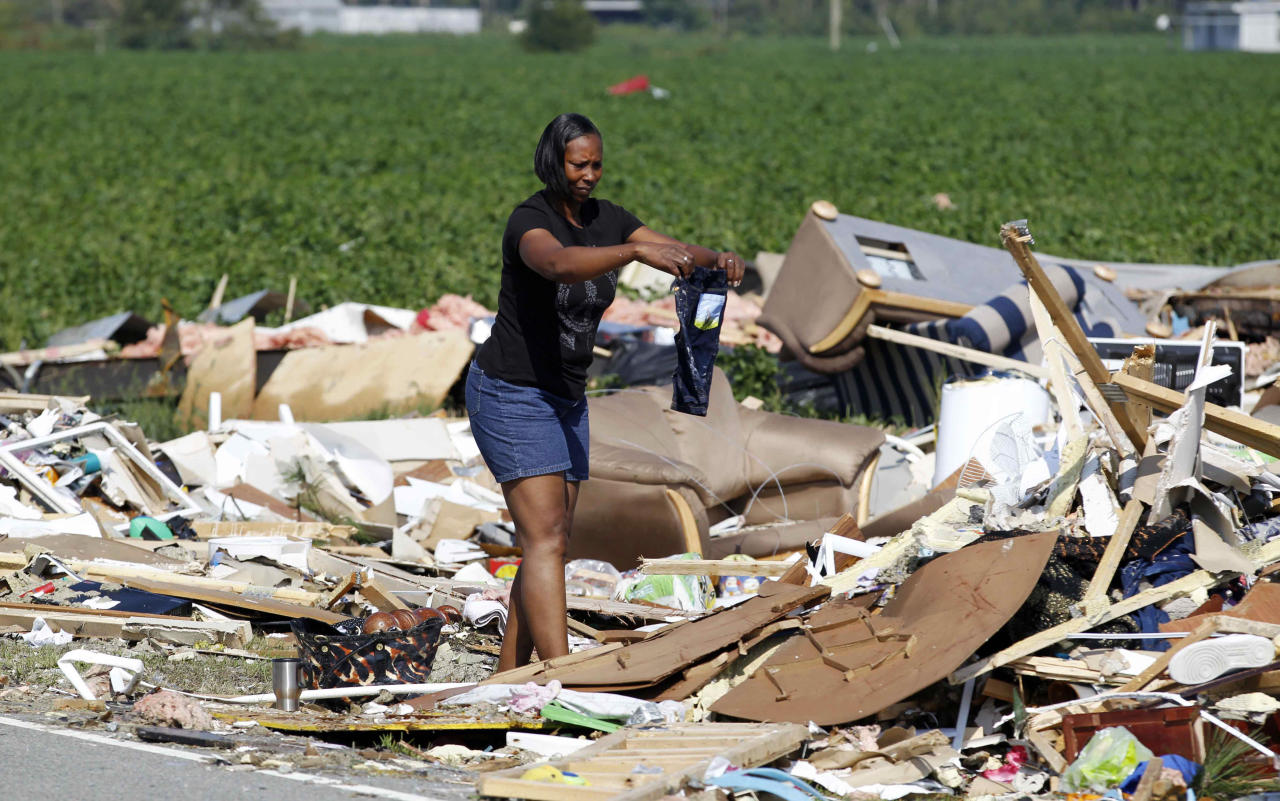 Laura Spencer tires to savage her grandson's clothes Sunday, Aug. 28, 2011 after her daughter's home was hit by Hurricane Irene Saturday in Columbia, N.C. The storm killed at least 14 people and left 4 million homes and businesses without power. It unloaded more than a foot of water on North Carolina and spun off tornadoes in Virginia, Maryland and Delaware. (AP Photo/John Bazemore)