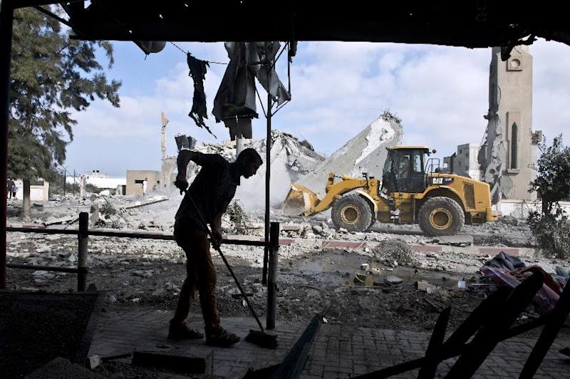 A Palestinian man sweeps the floor of his home that was damaged by an Israeli airstrike on August 25, 2014 in Beit Lahia in the northern Gaza Strip
