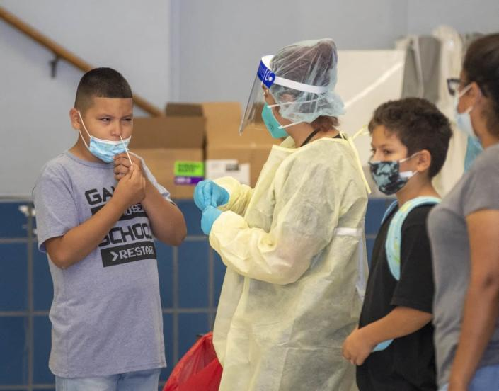 """<div class=""""inline-image__caption""""><p>A medical professional oversees as a fifth-grader gives himself a rapid COVID-19 test on the first day of school at Montara Avenue Elementary School in Los Angeles.</p></div> <div class=""""inline-image__credit"""">Allen J. Schaben / Los Angeles Times via Getty Images</div>"""