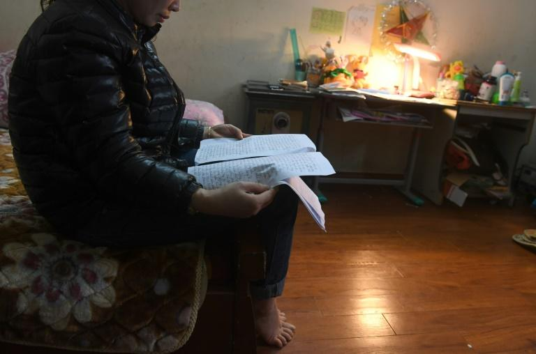 Nga, the mother of an eight-year-old abused girl, holds her hand-written letter to police asking for an investigation into her daughter's case
