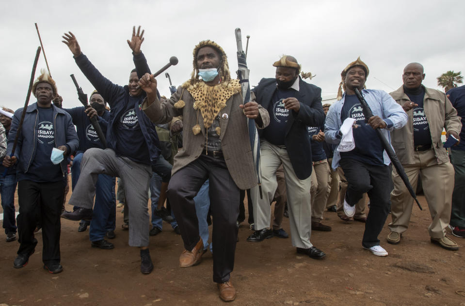 Zulu traditional men, sing and dance during a community and a local government campaign against Gender-Based Violence (GBV) and education on COVID-19, at a hostel in Katlehong, near Johannesburg, South Africa, Saturday, Nov. 28, 2020. (AP Photo/Themba Hadebe)