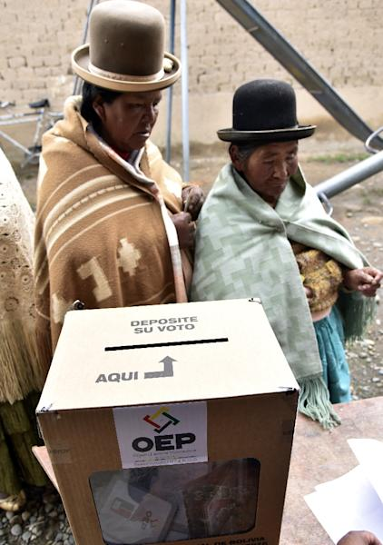 Two Aymara indigenous women wait to vote on February 21, 2016 in Huarina, 75 km from La Paz (AFP Photo/Aizar Raldes)