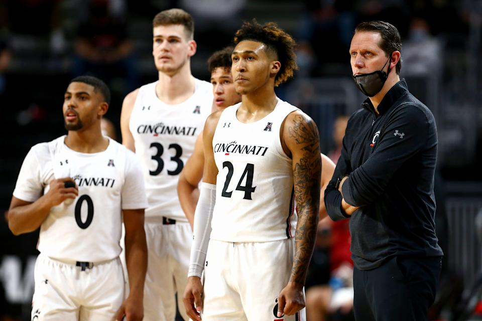 John Brannen and Cincinnati Bearcats players watch technical free throws in the second half of the game against Temple on Feb. 12 at Fifth Third Arena in Cincinnati. The Cincinnati Bearcats won the game, 71-69.