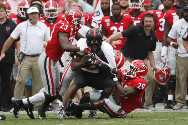 Arkansas State wide receiver Kirk Merritt (13) is dragged down by Georgia defensive backs Mark Webb (23) and J.R. Reed (20) In the first half of an NCAA college football game Saturday, Sept. 14, 2019, in Athens, Ga. (AP Photo/John Bazemore)