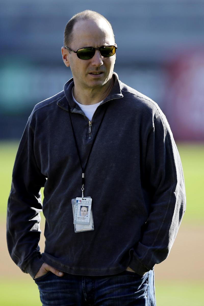 FILE - In this Feb. 16, 2013, file photo, New York Yankees general manager Brian Cashman watches a workout at baseball spring training in Tampa, Fla.  Cashman has broken his right leg and dislocated the ankle while parachute jumping from a plane in Florida. Cashman jumped with the U.S. Army Golden Knights in a plane from Homestead Air Reserve Base outside Miami, a fundraiser for the Wounded Warrior Project. He was hurt on his second jump Monday, March 4, 2013. (AP Photo/Matt Slocum, File)