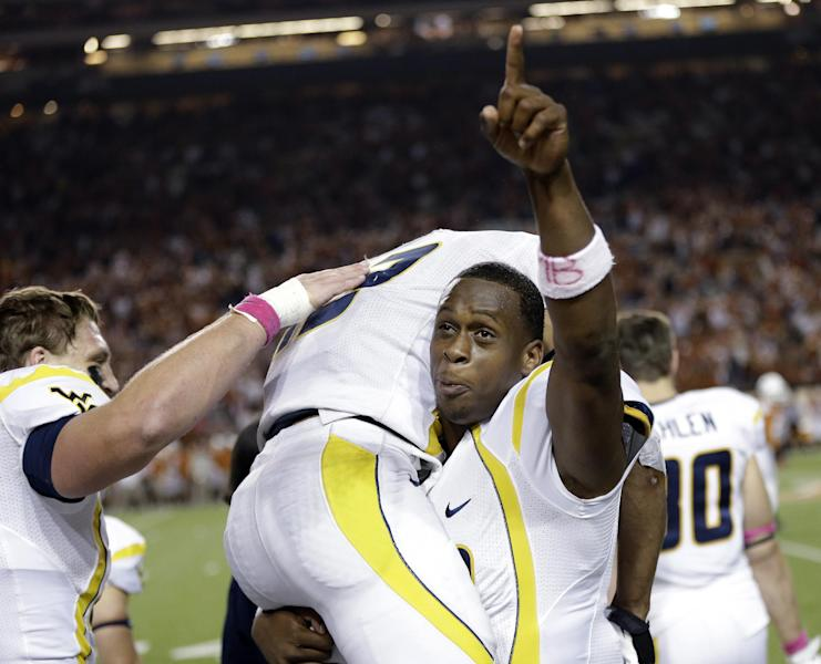 West Virginia's Andrew Buie, top, is lifted on the sideline by teammate Geno Smith after scoring against Texas during the fourth quarter of an NCAA college football game on Saturday, Oct. 6, 2012, in Austin, Texas. West Virginia won 48-45. (AP Photo/Eric Gay)