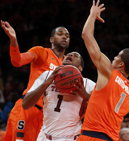 Temple's Khalif Wyatt (1) drives to the basket between Syracuse's James Southerland, left, and Michael Carter-Williams, right, during the first half of an NCAA college basketball game in the Gotham Classic at Madison Square Garden, Saturday, Dec. 22, 2012, in New York. (AP Photo/Jason Decrow)
